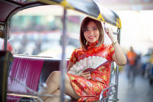 asian woman wearing chinese tradition clothes sitting in tuktuk passenger seat bangkok thailand