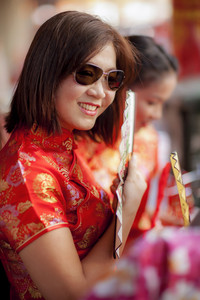 asian woman wearing chinese tradition suit and holding bamboo fan with toothy smiling face in bangkok china town