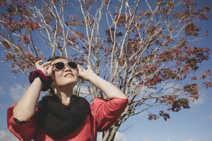 asian woman wearing sun glasses and toothy smiling against red leaves tree