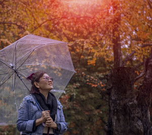 asian woman with raining umbrella standing in colorful park of japan season change to falls and winter