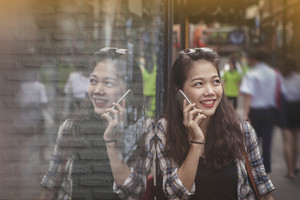 asian yonger woman toothy smiling face talking on mobile phone happiness emotion