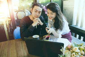 asian younger freelance man and woman working on computer in home office