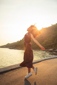 asian younger woman jumping and floating mid air against beautiful sun light