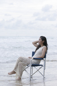 asian younger woman sitting on relaxing chair on sea beach vacation time