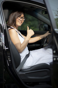 asian younger woman sitting on suv car driving seat toothy smiling face with self confidence