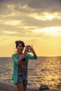 asian younger woman taking photograph by smart phone on sunset sea beach
