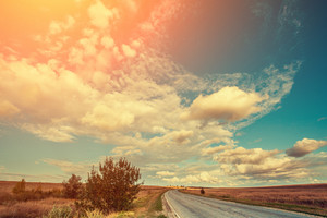 Asphalt road in the steppe. The blue cloudy sky. Summer sunny day