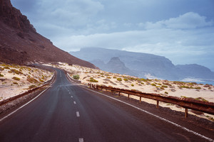 Asphalt road leads between black volcano erosion mountain and white sand dunes. Breathtaking coastline of Calhau, Sao Vicente Island Cape Verde