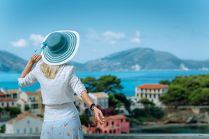 Assos in morning light. Young tourist woman wearing blue sunhat and white clothes admiring view of colorful tranquil village. Enjoying summer day travel vacation on Kefalonia, Greece