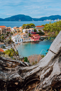 Assos village in Kefalonia, Greece. Calm blue bay water and colored traditional houses. Old snag in the front
