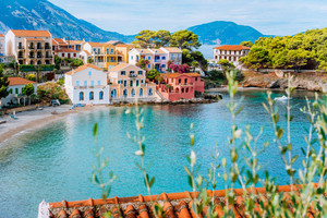 Assos village in Kefalonia, Greece. Turquiose bay, quite beach and colored traditional houses. Red roofs in front