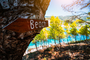 Assos village in morning light, Kefalonia. Greece. Beach wooden arrow sign on a pine tree showing direction to small hidden beach