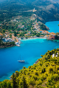 Assos village in morning light, Kefalonia. Greece. White lonely yacht in beautiful turquoise colored bay lagoon water surrounded by pine and cypress trees along the coastline