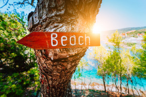Assos village in morning sun beam light, Kefalonia. Greece. Beach wooden arrow sign on a pine tree showing direction to small hidden beach