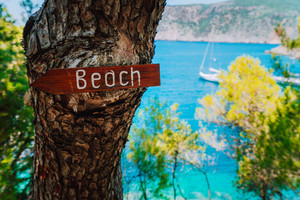 Assos village, Kefalonia. Greece. Beach wooden arrow sign on a pine tree showing direction to small hidden beach. White baot in sea background