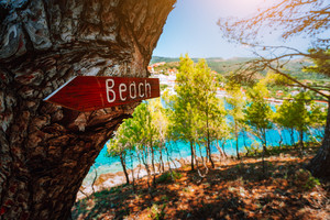 Assos village Kefalonia. Greece. Beach wooden arrow sign on a pine tree showing direction to small hidden beach