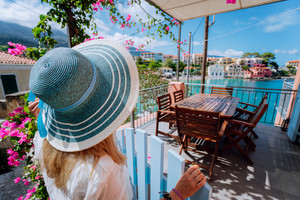 Assos village, Kefalonia, Greece. Female tourist in blue sunhat in front of cozy veranda terrace door admiring turquoise bay of Mediterranean sea and beautiful colorful houses