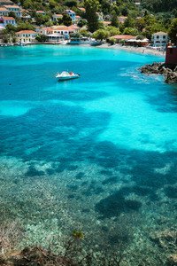 Assos village, Kefalonia Greece. Transparent turquoise emerald green sea water with dark pattern on bottom in lagoon