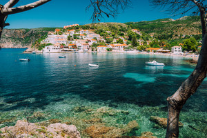 Assos village, Kefalonia Greece. View on turquoise transparent bay lagoon of Mediterranean sea. Surrounded by green pine trees. Blue deep pattern on bottom