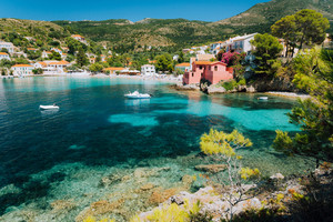 Assos village, Kefalonia Greece. View to cute bay with vivid colored houses and transparent turquoise water surrounded by green pine trees. Blue deep pattern on bottom