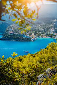 Assos village, Kefalonia. Greece. White yacht in blue bay framed by nature. Turquoise colored bay in Mediterranean sea surrounded by pine trees under bright sun beam light