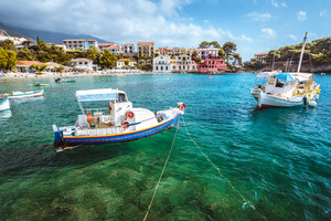 Assos village on Kefalonia island, Greece. White blue local boats at anchor in the emerald rippled sea water bay