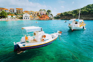 Assos village on Kefalonia island, Greece. White boats in the emerald rippled sea water bay