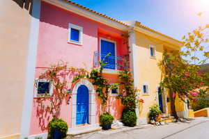 Assos village. Traditional colored greek houses with bright blue doors and windows. Blooming fucsia plant flowers growing around entrance welcome gates. Kefalonia island, Greece