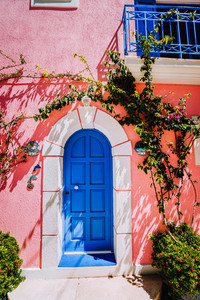 Assos village. Traditional lilac colored greek house with bright blue door and fucsie plant flowers around. Kefalonia island, Greece