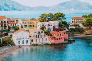 Assos village. Vivid colorful local house buildings close to transparent blue turquoise lagoon. Kefalonia, Greece