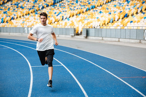 Athlete man running on a racetrack at a stadium