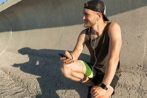 Athletic young sportsman listening to music with earphones while resting after work out outdoors