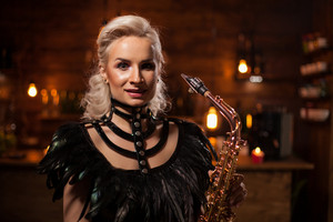 Atractive young woman performing jazz on saxophone in a pub. Female musician. Jazz concert.