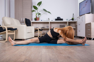Attactive young woman being flexible during her home training. Home healthy training.