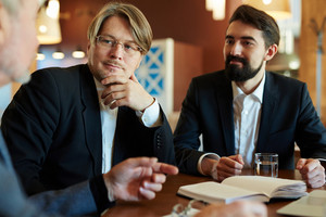 Attentive men listening to colleague explanation