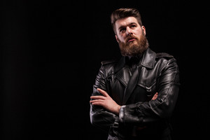 Attractive bearded man keeping his arms crossed over blac background. Stylish man. Biker jacket. Stylish hair style.