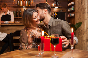 Attractive bearded man kissing his girlfriend cheek after recieving a birthday gift. Young couple looking happy