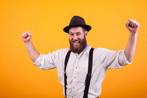 Attractive bearded man smiling and wearing a black hat rising his fists over yellow background. Pure happines. Excited man. Stylish beard.