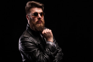 Attractive bearded man with styish glasses over black background.