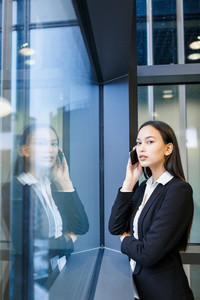 Attractive businesswoman looking at camera while standing at office window and talking on phone, portrait shot