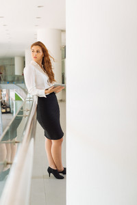 Attractive businesswoman with tablet computer leaning  on railing in office building and looking away