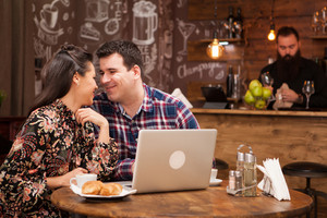 Attractive couple at a business meeting in the restaurant disucssing working moments at lunch time. Hipster pub.