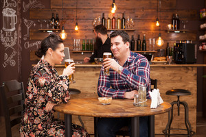 Attractive couple drinking beer in a beautiful hipster pub. Happy couple.