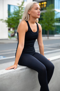Attractive exhausted young woman resting during her workout in city