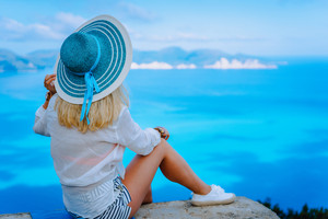 Attractive female tourist with turquoise sun hat enjoying amazing azure seascape, Greece. Cloudscape shadows on the sea surface in background