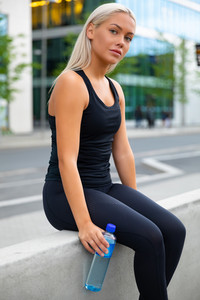 Attractive fit young woman dressed in black sportswear sitting outdoors