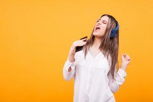 Attractive girl enjoying music from her headphones over yellow background. Enjoying herself