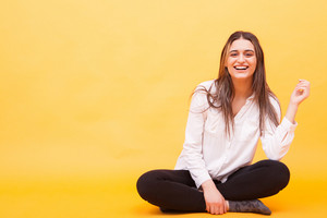 Attractive girl in white shirt smiling and sitting down over yellow background. Sweet girl