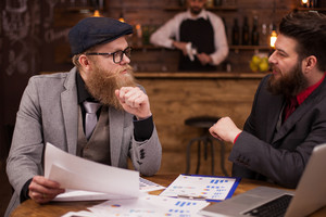 Attractive men talking with his advisor about his business in a coffee shop. Handome men. Men in suit.