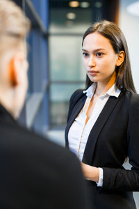 Attractive mixed race entrepreneur looking at her business partner with concentration while discussing details of their agreement, over shoulder view